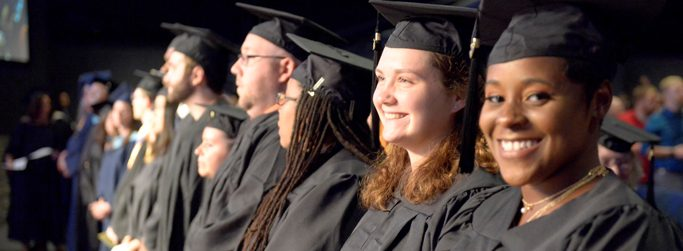 Pic of graduates smiling at the camera